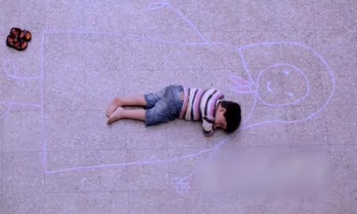 一个孩子用粉笔画出一个妈妈,然后躺进妈妈的怀抱